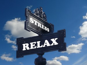 """A """"Stress"""" sign on top of a""""Relax"""" sign, blue sky with white clouds in the background"""