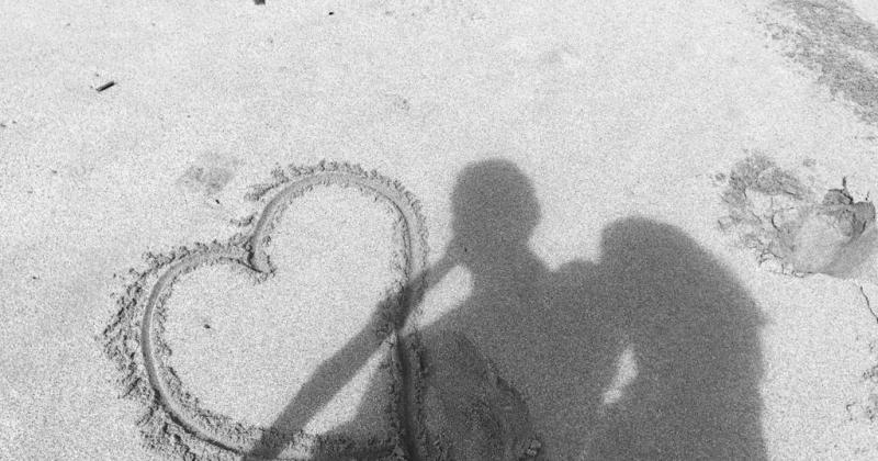 La sombre de una pareja sobre un corazon dibujado en la arena
