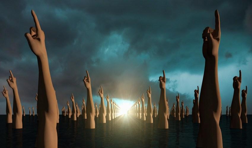 Un monton de esculturas de brazos con el dedo indice extendido sobre una tierra negra bajo un cielo nublado con un destello de luz al fondo