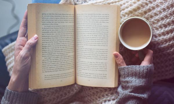 libro abierto por una manos ancianas junto con un café