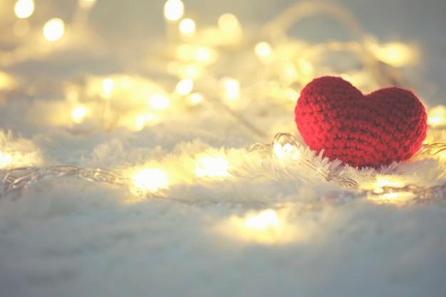 un corazón rojo de punto sobre la nieve y unas luces de navidad de color blanco