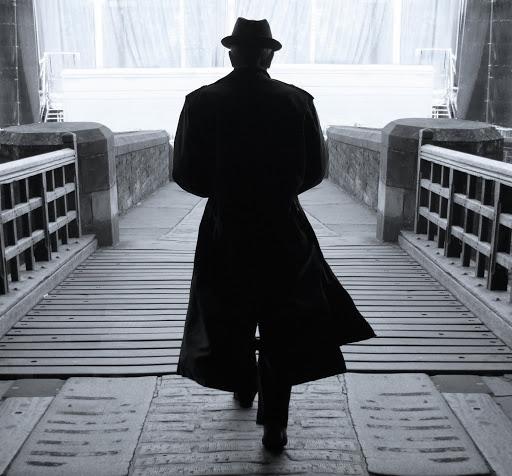 Leonard Cohen despaldas con su característico sombrero y una gabardina cruzando un puente de madera.