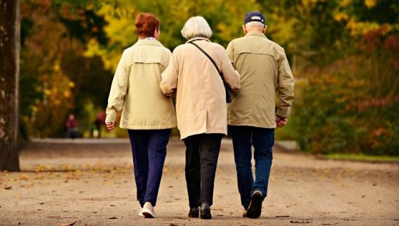 Una mujer de pelo canoso camina del brazo de otra mujer de pelo pelirrojo y de un hombre de pelo cano alejándose los tres del fotógrafo
