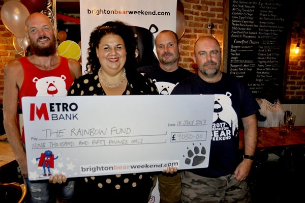Maria Baker from Rainbow Fund grants committee accepts cheque for £9.050 from Brighton Bear Weekend committee
