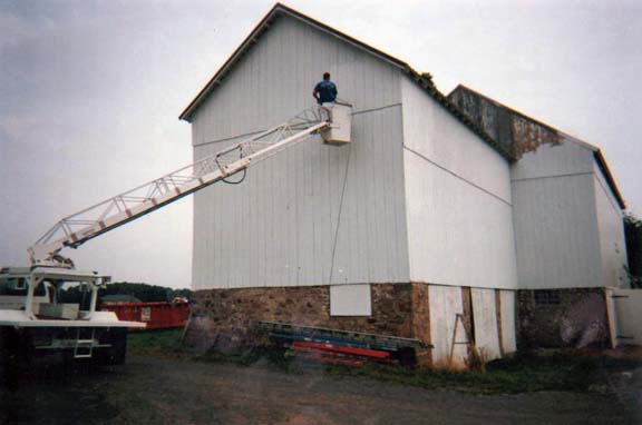 Commercial Exterior Painting Contractor Paints A Barn From A Ladder Truck