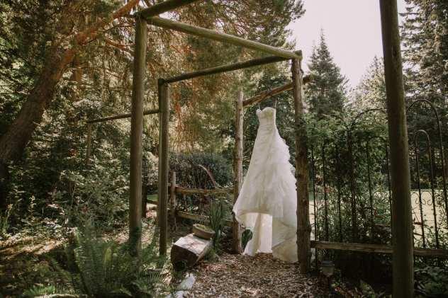 anacortes wedding venue wisteria gardens wedding dress on trellis in the sunlight