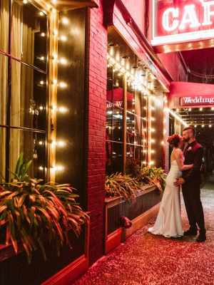 seattle wedding photographer at Lake union cafe at night under the sign bride and groom kissing