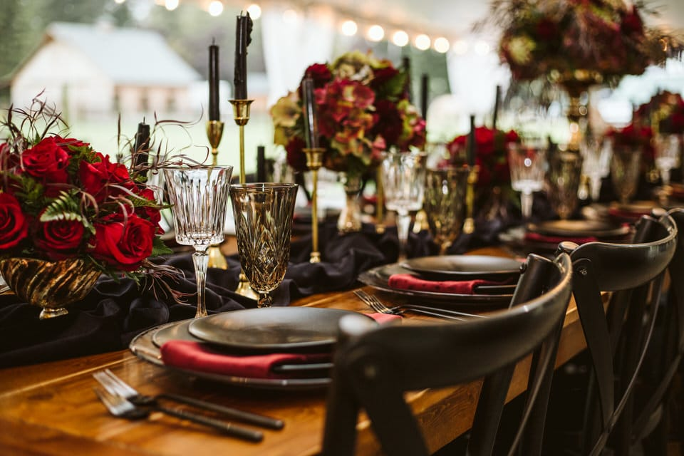 black red and gold wedding reception table set up with red roses black candles and gold accents at gray bridge snohomish wedding photography