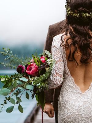 Elopement Photography in Washington State Lake Crescent Olympic National Park December Wedding with Blue Lake and Lace Dress on Bride with King Protea Flowers in her Bridal Bouquet