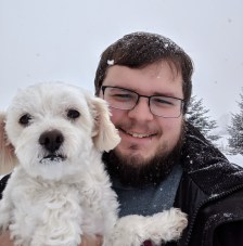 Adam holding a small white dog in a snowy Vermont landscape