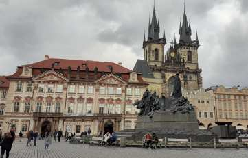 One end of the Old Town Square, with prime examples of Prague Baroque architecture, the Jan Hus Memorial, and the turreted Gothic towers of the Church of Mother of God before Týn in the background.