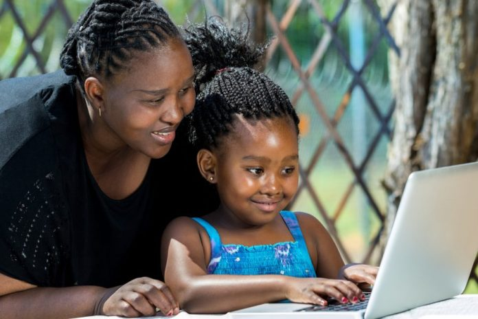 A teacher guiding a child on how to use a laptop. Photo Alamy