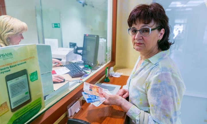 Женщина в банке вносит деньги на счет