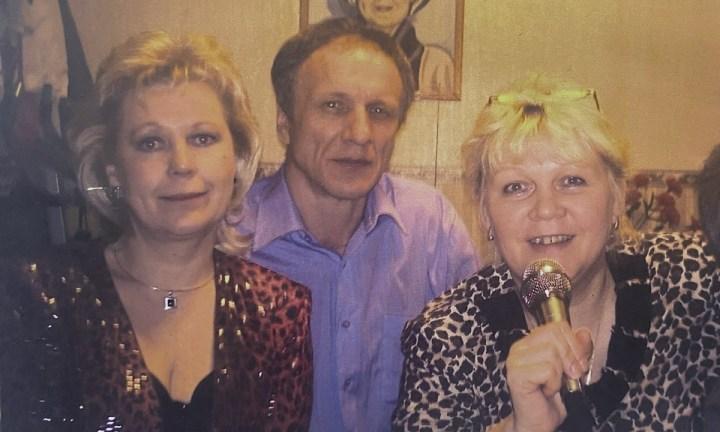 Нарядные мужчина и женщины поют в микрофоно