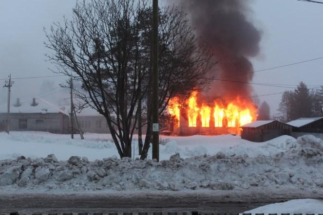 Здание полыхает огнем на фоне сугробов