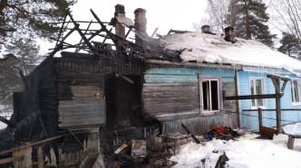 Сгоревший деревянный дом с синими стенами в снегу