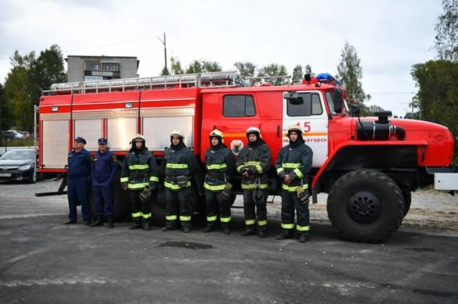 Пожарные в форме стоят на улице на фоне красной пожарной машины