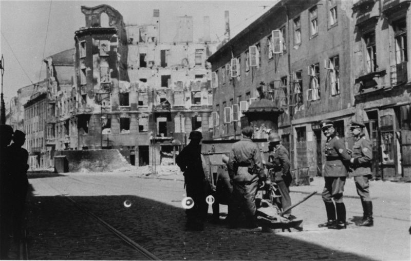 A German gun crew prepares to shell the ruins of a building during the suppression of the Warsaw ghetto uprising.