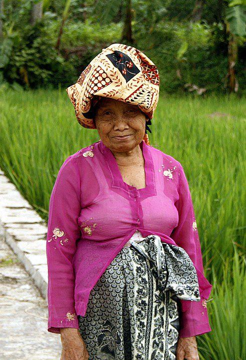 A friendly Sundanese elderly woman on her way at ricefield paddy, wearing kebaya, kain batik and batik headcloth