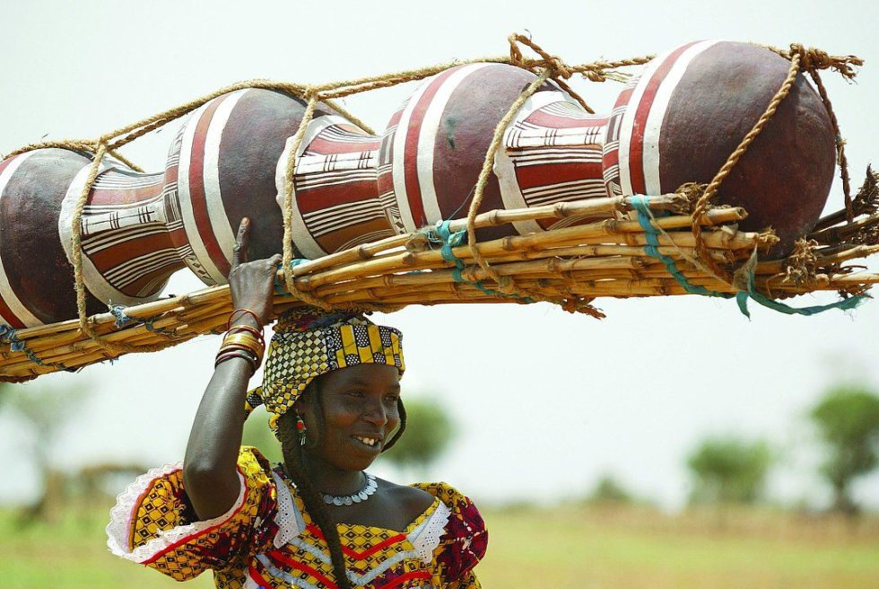 Woman carrying traditional water pots for sale in Niger