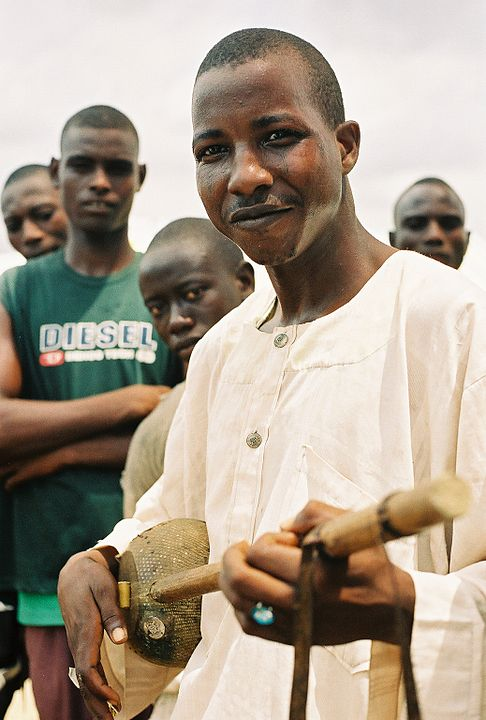 A Hausa man playing a xalam, a two-stringed instrument