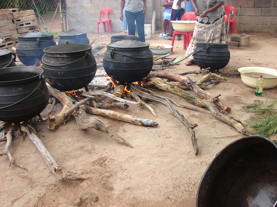 Cooking seswaa in pots over open fires