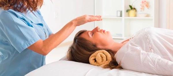 mulher em maca recebendo reiki - terapia holística
