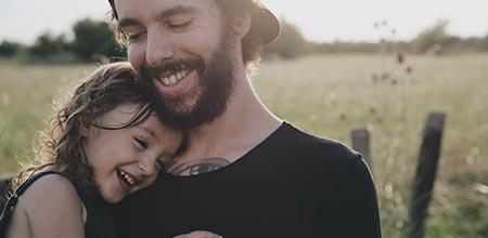 pai com filha no colo em paternidade saudável