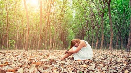 mulher sentada no chão em folhas secas, com rosto apoiado nas pernas, se sentindo menor com a ferida da alma da humilhação
