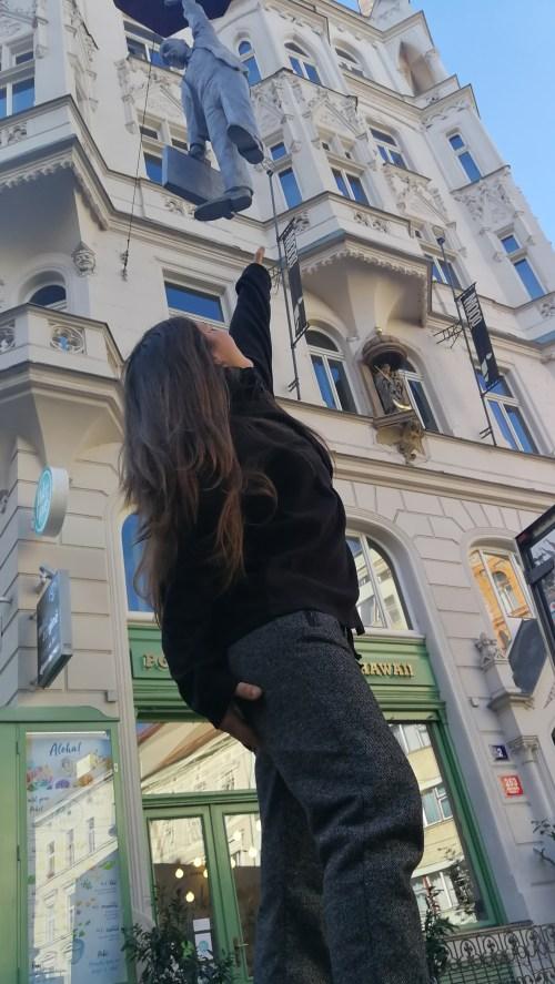 Estatua con paraguas colgada de las calles de Praga.