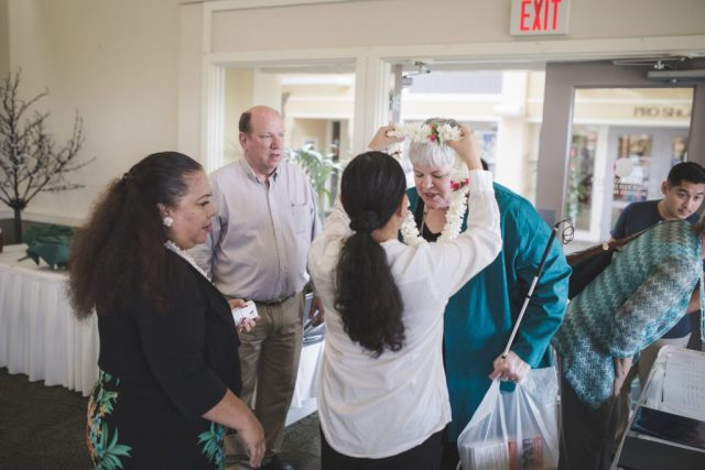 A woman with a white cane leaning forward to receive a lei that's being gifted.