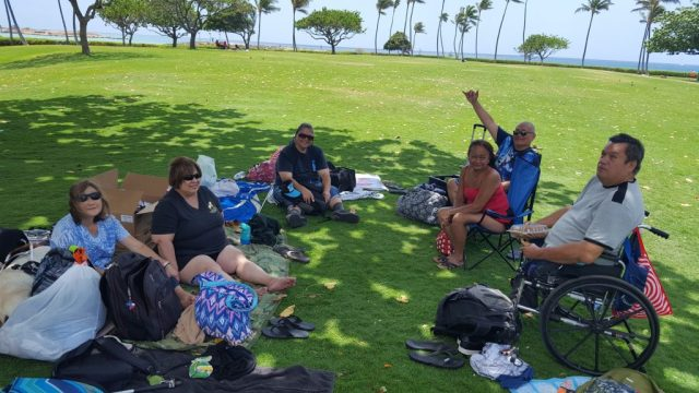 A group of clients gathered at Ko'olina beach park for lunch and sun-time.