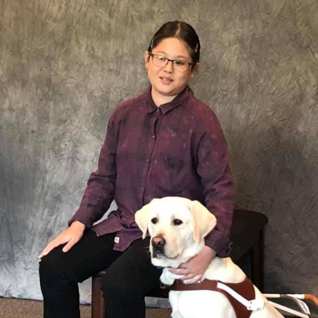 A young woman sits in a purple button-up shirt with her yellow labrador guide dog sitting by her side. Her arm is around the dog's shoulders.