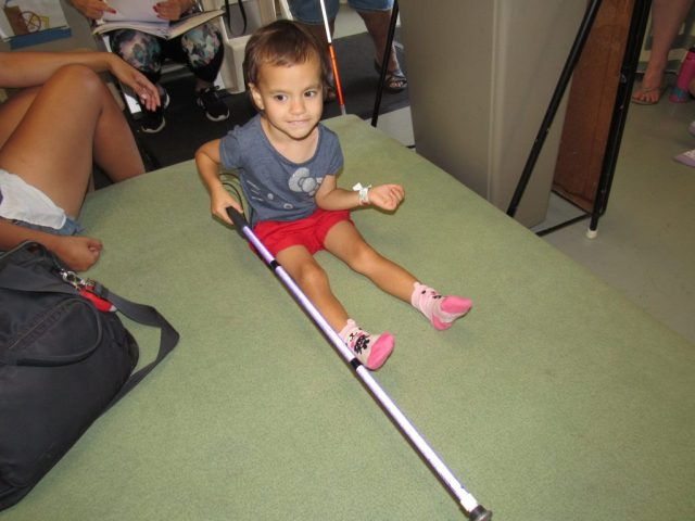 A young girl sits in pink socks getting ready for a trampoline experience. She has her white cane out.