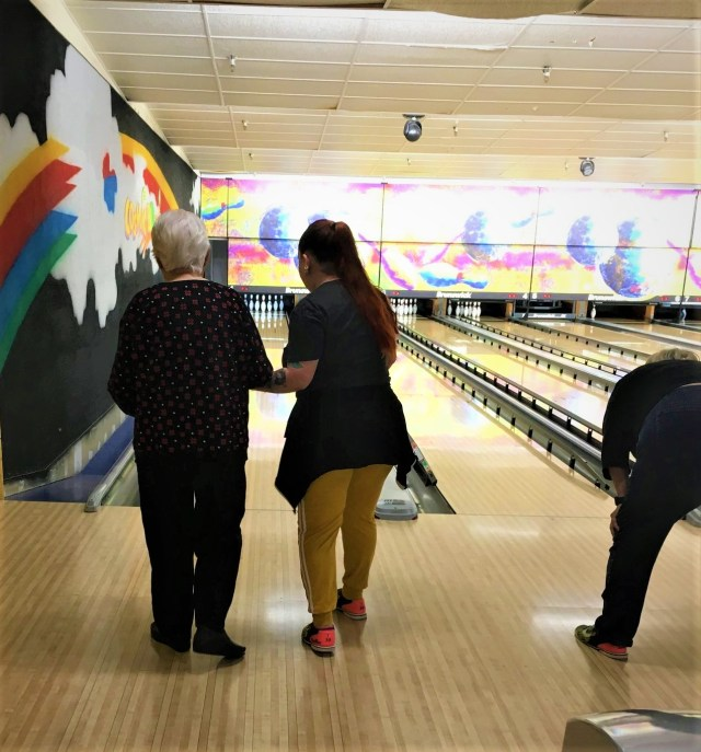 A young woman guides an older woman toward a lane at a bowling alley.