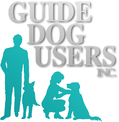 """Guide Dog Users Inc. Logo. In this image is a man standing next to his dog and to his immediate right is a woman kneeling next to her dog. Immediately above them all are the words """"Guide Dog Users Inc."""