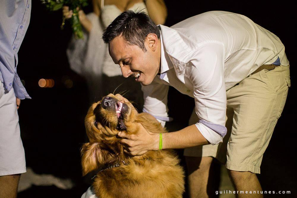Foto de Casamento na praia de Larissa e Ronaldo noivo brinca com cachorro feliz