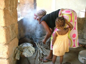 Bountourabi watches her mom cook. She likes to help and often 'plays' cooking and cleaning.