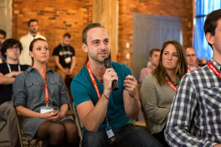 """A photo of an audience member holding a microphone, published as part of """"3 Reasons Why I Invite UX Professionals Into My Classroom"""""""