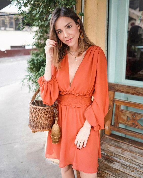 vestido terracota cutro com decote e bolsa de palha