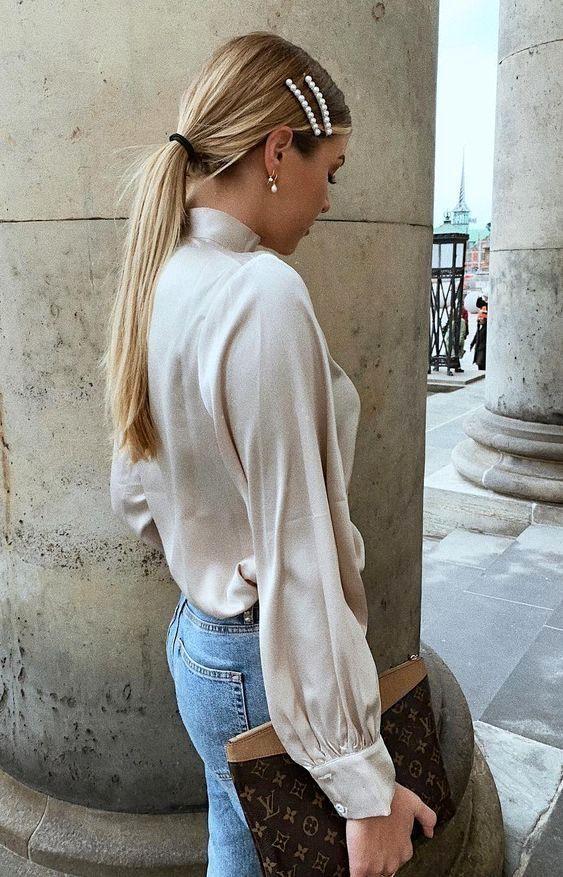 presilha de pérosas, camisa de cetim branca e calça jeans