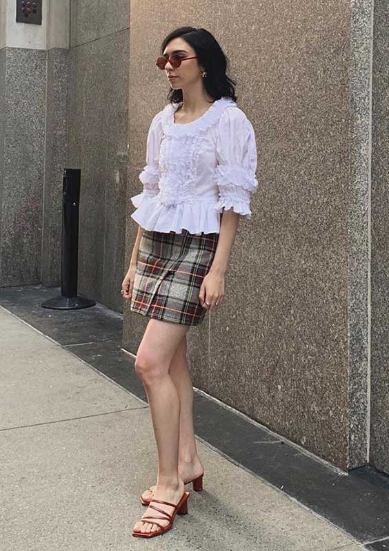 blusa branca com babados e mangas bufantes, minissaia xadrez