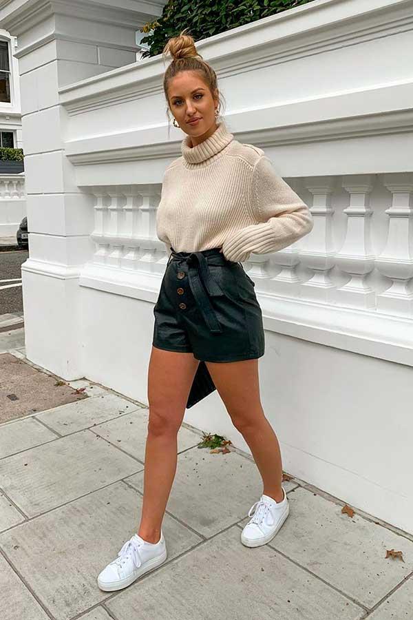 produções básicas, suéter bege de gola alta, short de couro e tenis brnco