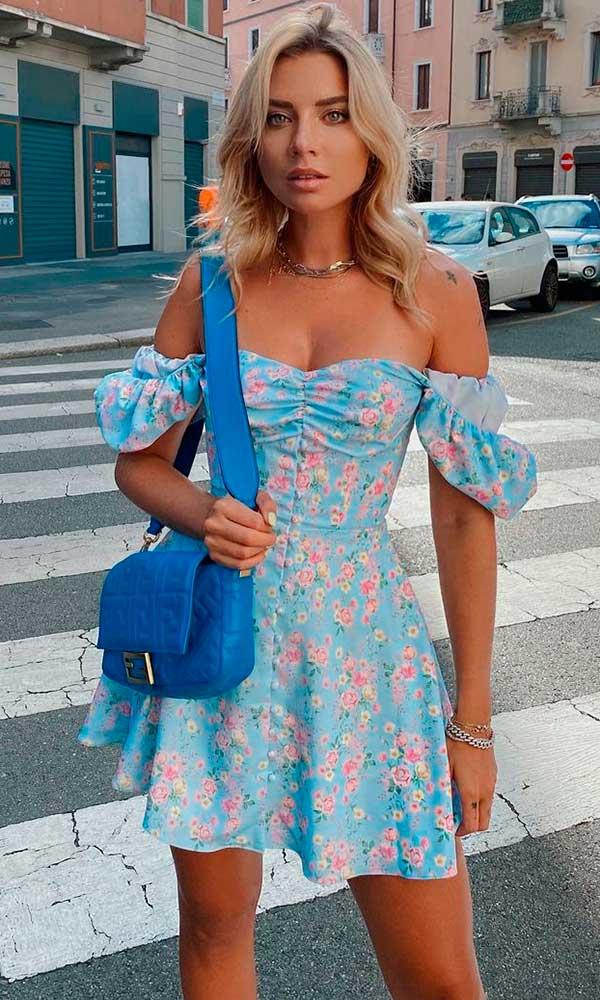 vestido floral com top ombro a ombro e bolsa azul