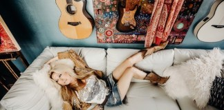 woman on couch with guitars on wall