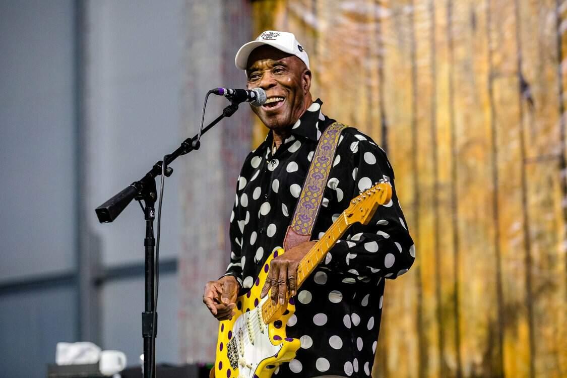 Buddy Guy se apresentando no New Orleans Jazz & Heritage Festival, em 2018. Sorrindo e com de praxe, com sua camisa e guitarra stratocaster de bolinhas