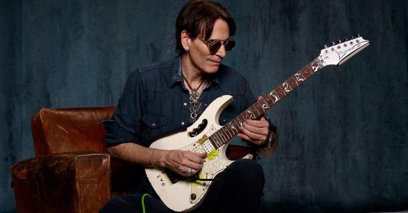 Steve Vai tocando guitarra sentado em um sofá