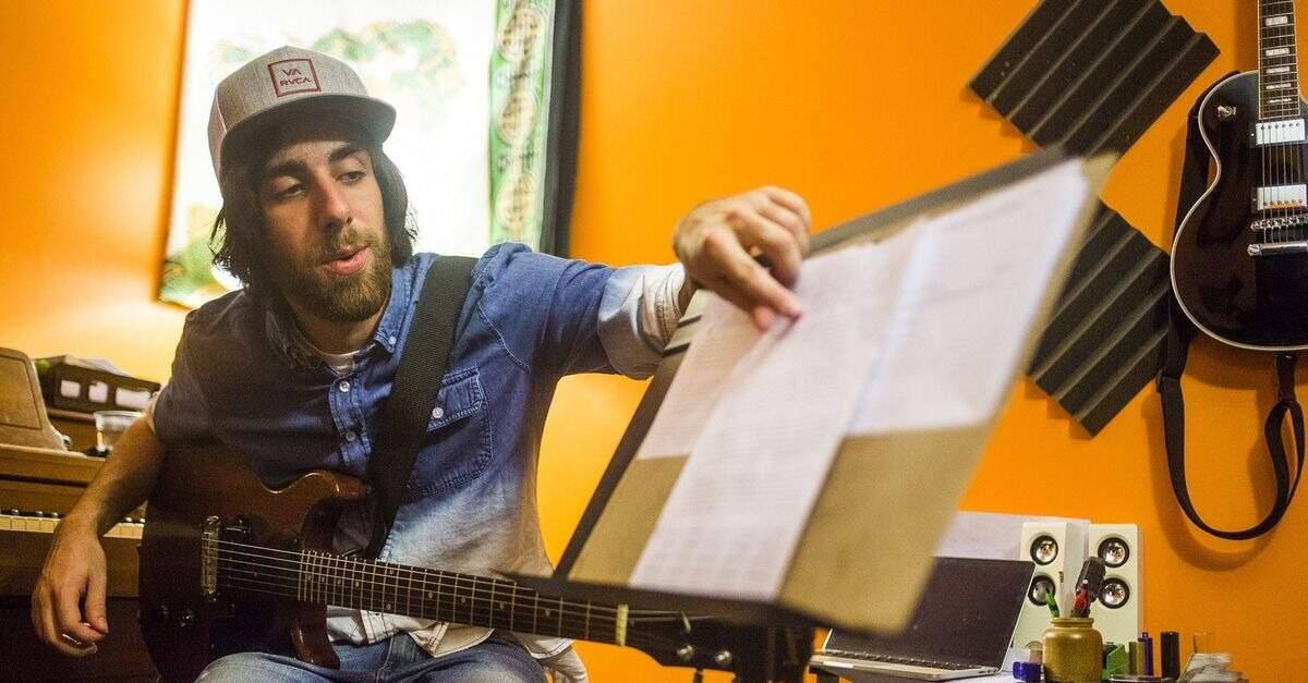 Joey Gaydos Jr. sentado com uma guitarra