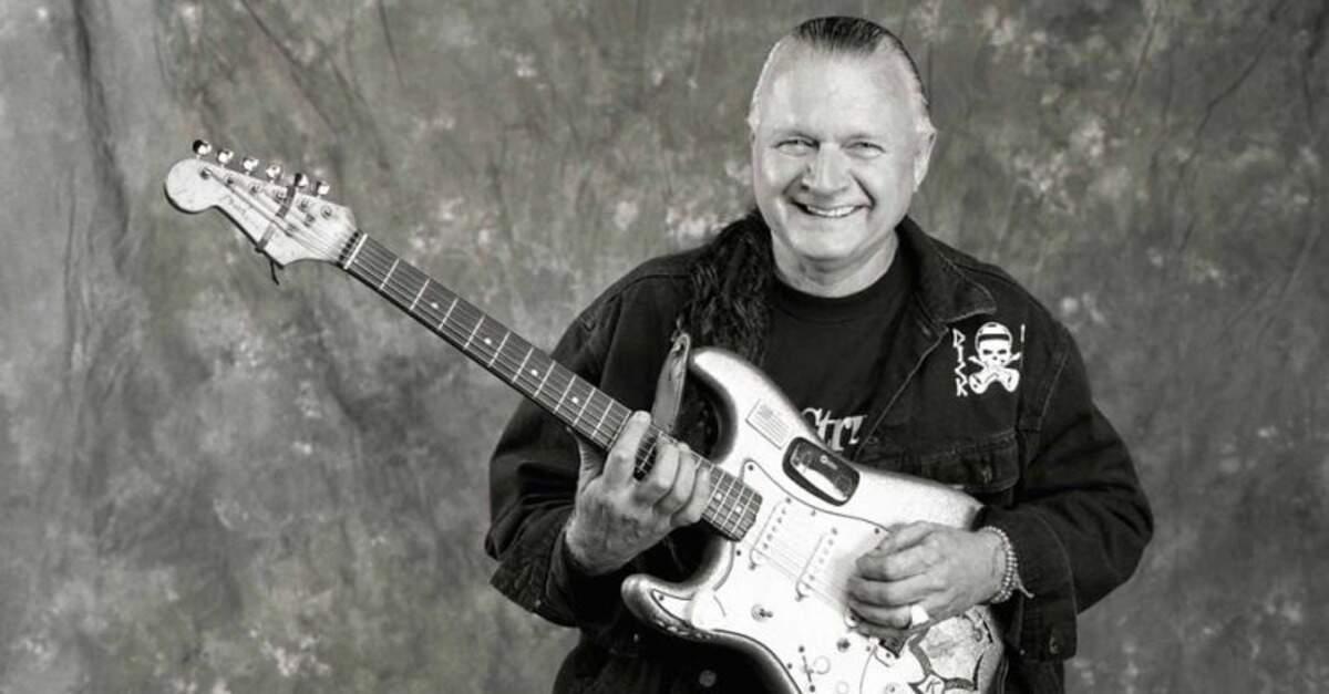 Dick Dale segurando uma guitarra e sorrindo