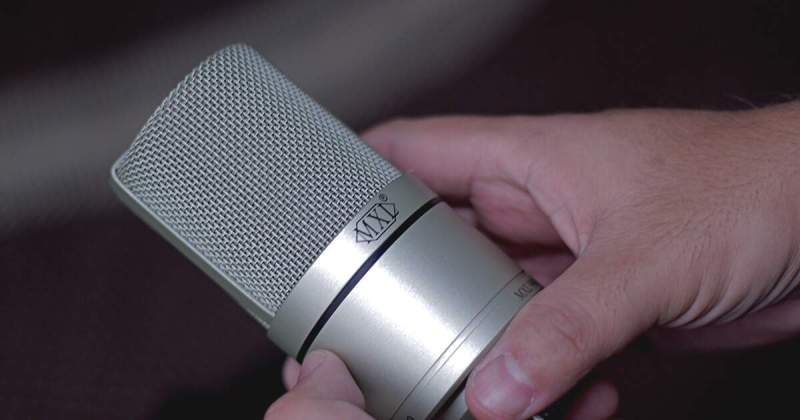 Foto do microfone MXL 990 nas mãos do guitarrista Kleber K. Shima